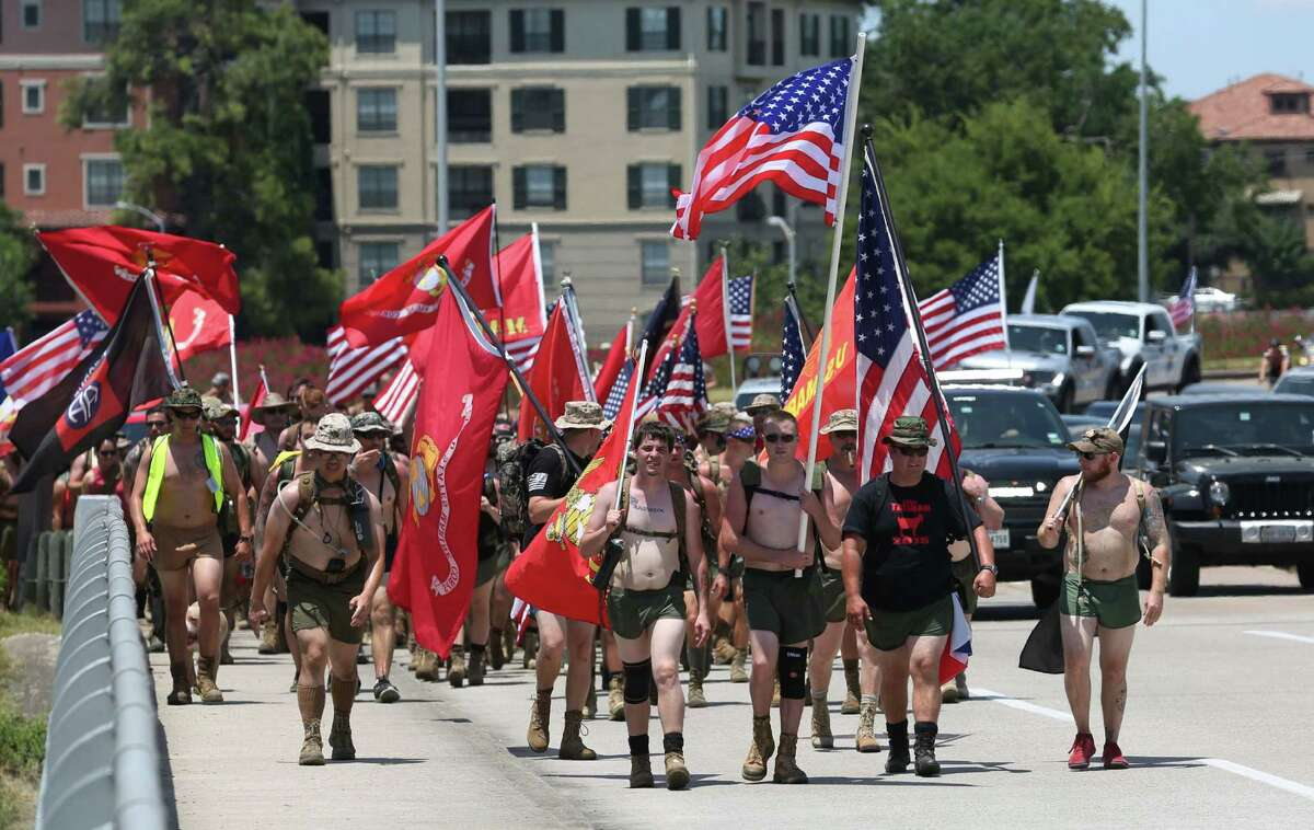 From left, with flags, Tyler Vaughn, Brian Chandlers, William Rutherford and Derek Cirilo, all Marines veterans, lead a group down Waugh Drive to Pimlico Irish Pub Saturday, Aug. 1, 2015, in Houston. The group will travel 22km to raise awareness about PTSD and suicides among veterans, which claim 22 lives each day.