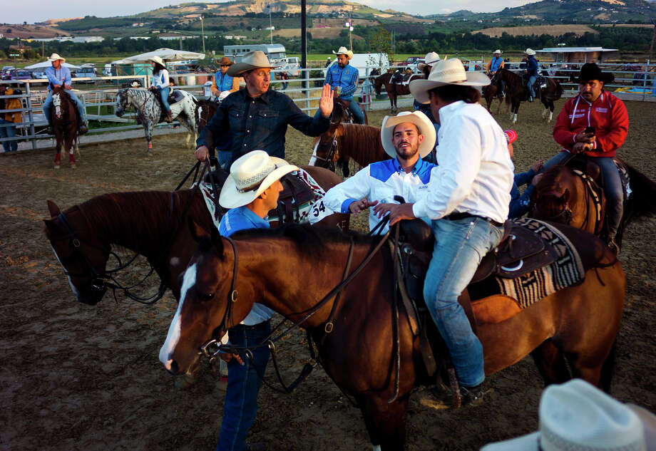 Participants in team penning, top, discuss strategies as they wait for their turn in Piane Vomano on the outskirts of Notaresco, central Italy, while Veruska Di Salvatore waits her turn to participate in the same team penning event. Photo: Domenico Stinellis / Photos By Domenico Stinellis / Associated Press / AP