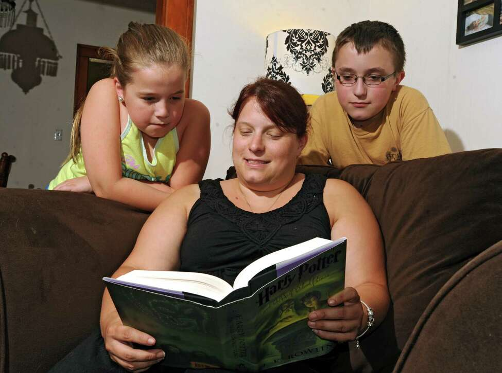 Simone Treffiletti reads with her kids Kadence, 11, left, and Tyler, 14, at their new home on Tuesday, July 28, 2015 in Lansingburgh, N.Y. (Lori Van Buren / Times Union)