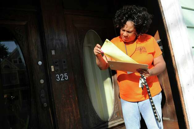 Cathy Edmondson, City School District of Albany community engagement coordinator, looks through her list of names as she stops by a home on Livingston Avenue on Thursday, July 30, 2015, in Albany, N.Y. The school district was registering children who had previously attended Brighter Choice Charter School. Cindy Schultz / Times Union) Photo: Cindy Schultz / 00032809A
