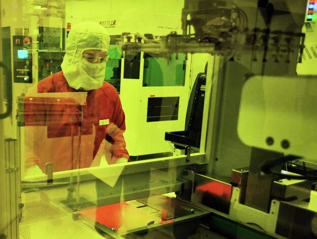 Technician Justin Herne loads flex panels into developer in a cleanroom of the digital x-ray detector factory at GE Healthcare Friday July 31, 2015 in Troy, NY. (John Carl D'Annibale / Times Union) Photo: John Carl D'Annibale / 10032850A