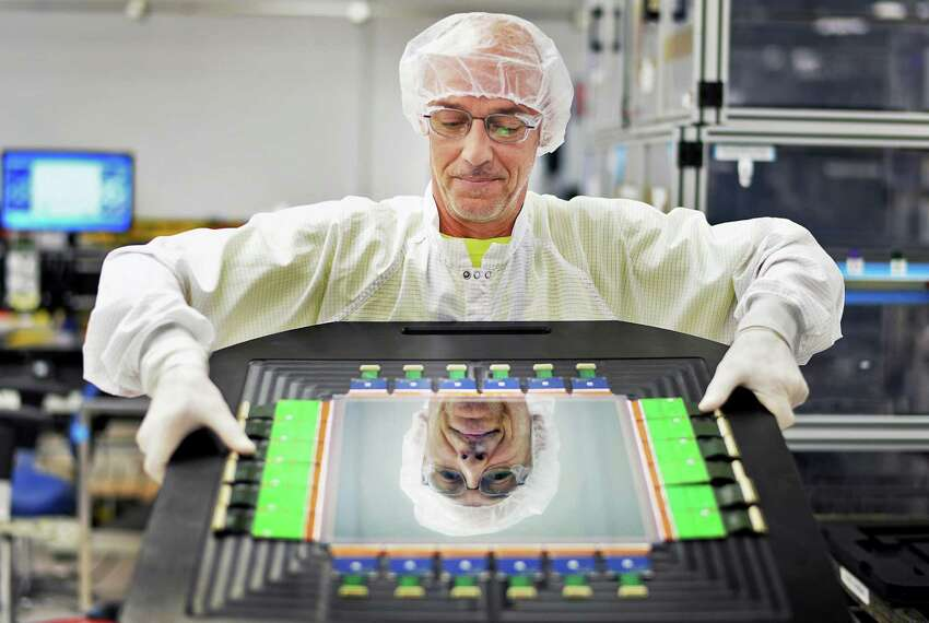 Fabrication technician Mark Skriptshak with a 31cm combo digital detector in a cleanroom at the digital x-ray detector factory at GE Healthcare Friday July 31, 2015 in Troy, NY. (John Carl D'Annibale / Times Union)