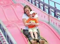 Aidan Larson, 4, lets out a scream while sitting in the lap of his mother, Allison Larson, of Stamford, as the duo rode the slide during the Harbor Point Summerfest to benefit the Young Mariners Foundation at Harbor Point in Stamford Saturday. Fred Lorthioir, treasurer of the Young Mariners Foundation, said the organization hoped to raise between $10,000 and $20,000 to benefit the nonprofit that focuses on improving the quality of young mariners through after-school programs focused on improving life skills and academic achievement.