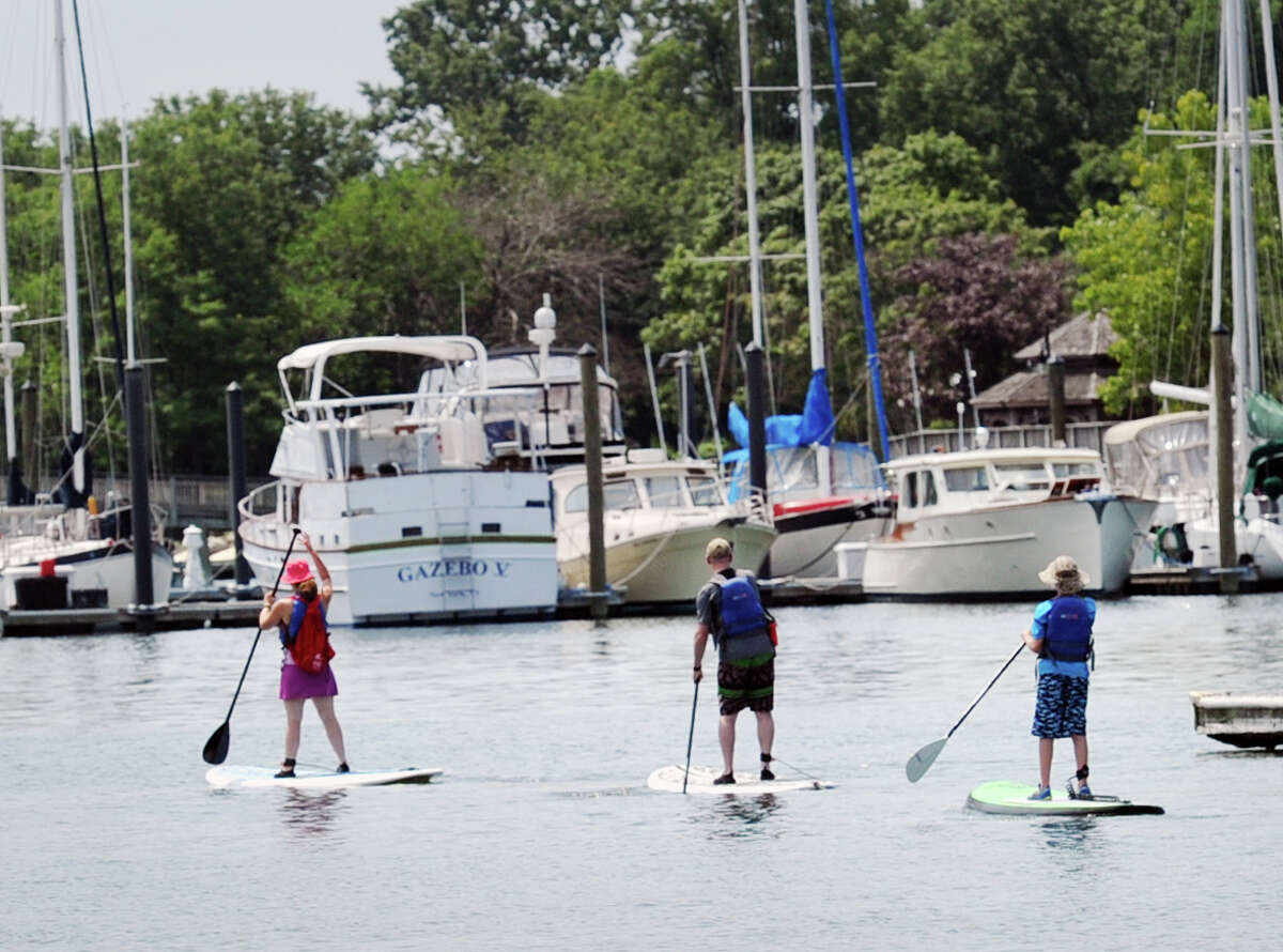 The Lapine family, of Stamford, from left, Eve, her husband, Seth, and their son, Garret, paddle board in Stamford Harbor during the Harbor Point Summerfest.