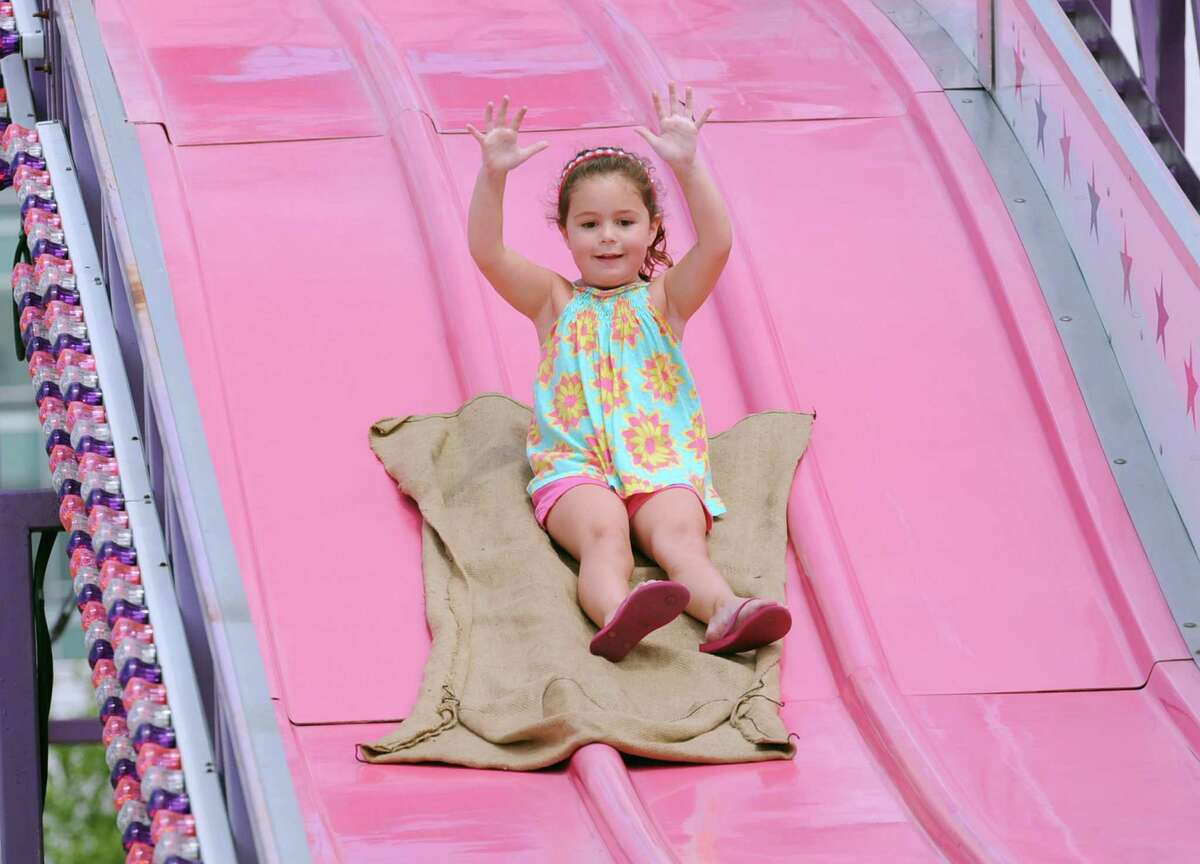 Sadie Golus, 5, of Darien, rides the slide during the Harbor Point Summerfest to benefit the Young Mariners Foundation at Harbor Point, Stamford, Conn., Saturday, Aug. 1, 2015. Fred Lorthioir, treasurer of the Young Mariners Foundation said that the organization hoped to raise between $10,000 - $20,000 to benefit the non-profit that focuses on improving the quality of young mariners through after-school programs focused on improving life skills and academic achievement.