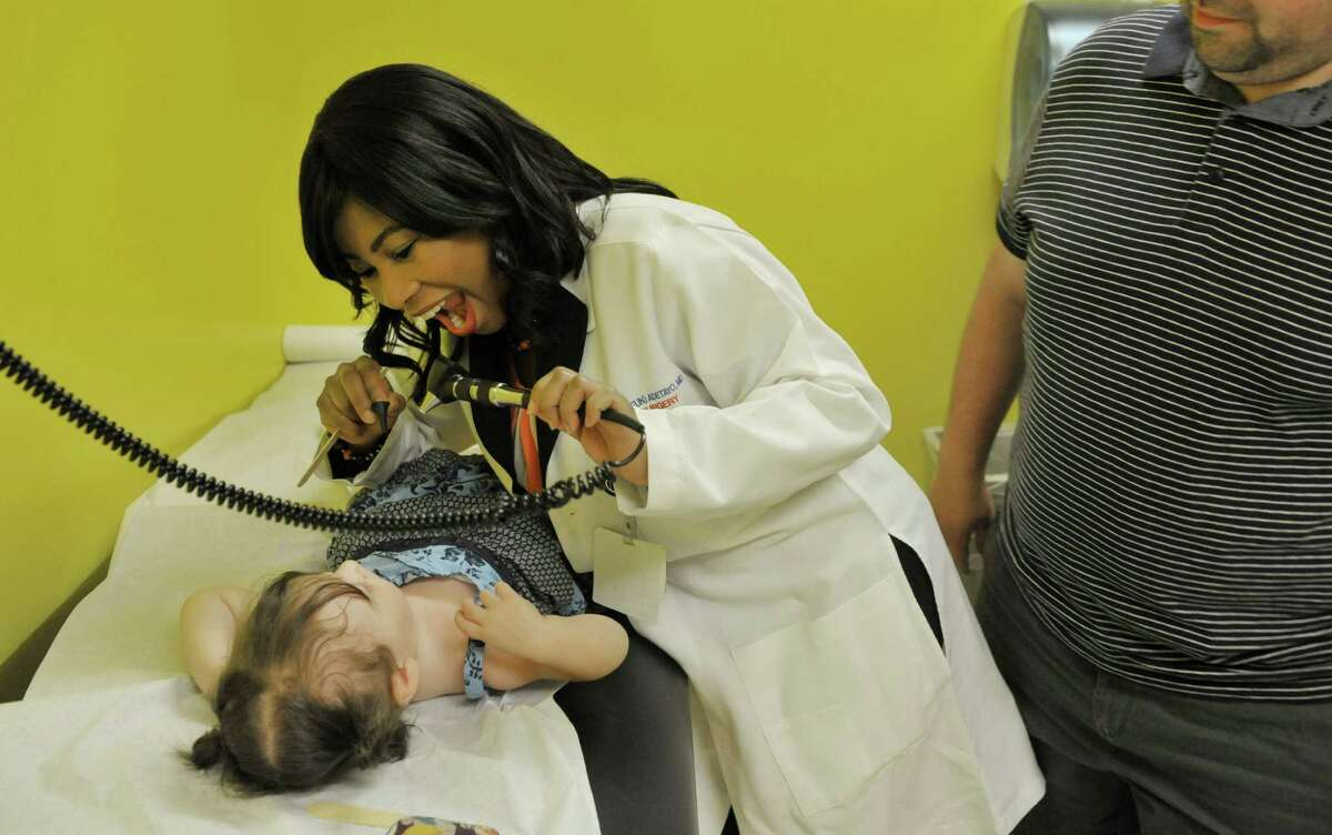 Dr. Oluwaseun Adetayo, director of the Cleft-Craniofacial Center at Albany Med., tries to get Amalia Delaloye, 19 months old, to open her mouth during an office visit on Monday, July 27, 2015, in Albany, N.Y. Amalia had surgery for cleft palate. (Paul Buckowski / Times Union)