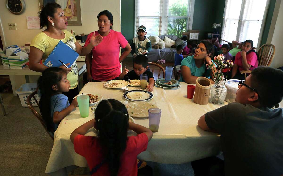 Yanira Lope Lucas (left), who's an immigrant from Guatemala, gives instructions to mothers and their children, all of whom were released recently from detention centers in South Texas.