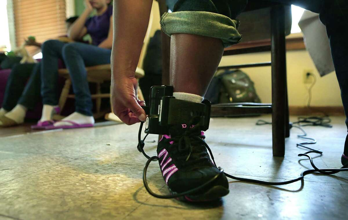 An immigrant woman staying at the Mennonite house plugs in the ankle bracelet that she was made to put on before leaving a south Texas detention center. Close to 30 mothers and children were housed at the Mennonite House on Wednesday, July 29, 2015.