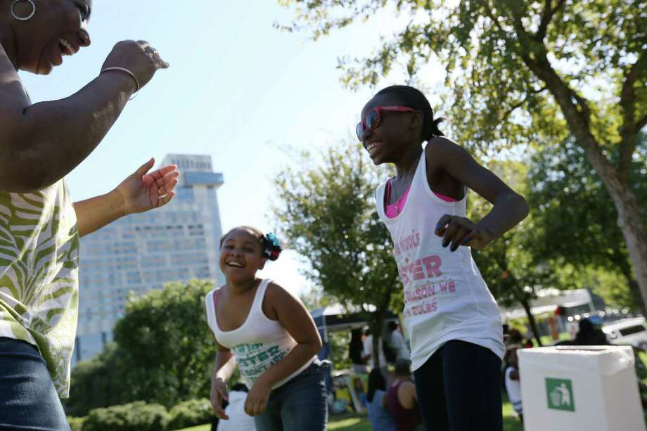 Courtney Thomas, 11, right, dances with Chanelle Matthews, 8, and Estella Rencher at the Houston Black Heritage Festival at Discovery Green Saturday, Aug. 1, 2015, in Houston. Photo: Jon Shapley, Houston Chronicle / © 2015 Houston Chronicle