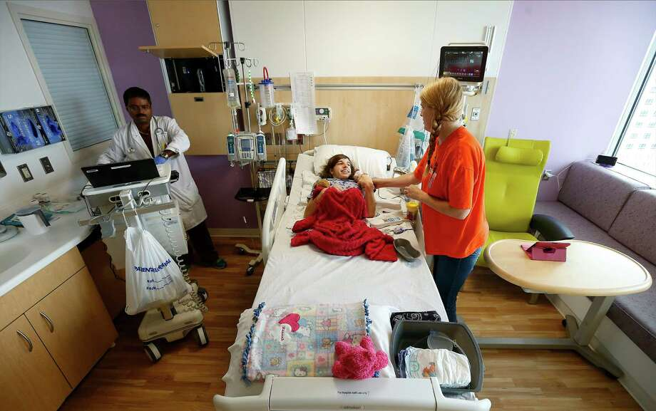 Respiratory therapist John Puthen (left) wraps up treating Hanna Baker, 16, who has a form of spina bifida while Hannah's mother, Tammy, tends bedside at the Children's Hospital of San Antonio. Photo: Kin Man Hui /San Antonio Express-News / ©2015 San Antonio Express-News