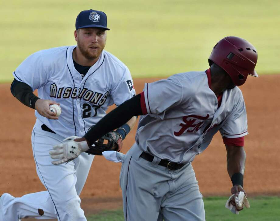 San Antonio Missions second baseman Taylor Lindsey chases Frisco RoughRiders runner Lewis Brinson in a rundown during Texas League action at Wolff Stadium on Aug. 1, 2015. Photo: Billy Calzada /San Antonio Express-News / San Antonio Express-News