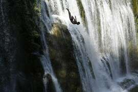 A competitor dives during the international waterfall jumping competition in the old town of Jajce, 250 kms west of Sarajevo, Bosnia, on Saturday, Aug. 1, 2015. A total of 25 competitors took part in the jump at 20 meters high. (AP Photo/Amel Emric)