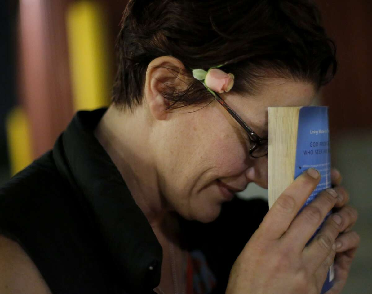 Laura Jordan holds a copy of the Bible placed at her daughter's memorial to her forehead at the Tannery Arts Center in Santa Cruz, California, on Saturday, Aug. 1, 2015.
