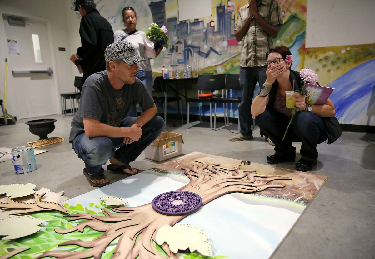 Laura Jordan (right) covers her mouth with her hand at the sight of a project a few residents, including Adrian Rasmussen (left), are creating in memory of her daughter at the Tannery Arts Center in Santa Cruz, California, on Saturday, Aug. 1, 2015.