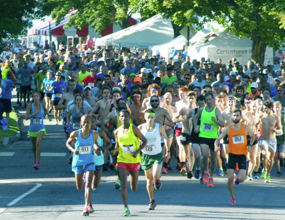 Eventual 8-mile champion Mengistu Nebsi (3), in the yellow shirt, quickly establishes his position among the frontrunners Saturday as the field of nearly 500 heads north along the Village Green to kick off the 48th edition of the New Milford 8-mile road race and the concurrent 13th annual Village Fair Days 5K. Settling in for a strong run, in the orange shirt, is New Milford High School graduate David Hunt (357), who went on to claim honors as the first New Milford 8-mile finisher. July 25, 2015 Photo: Norm Cummings / Norm Cummings / The News-Times