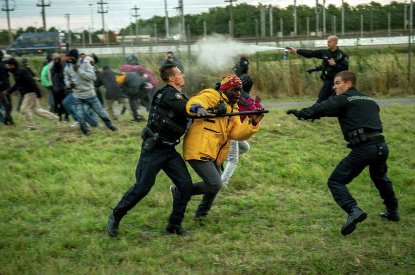 French gendarmes try to stop migrants on the Eurotunnel site in Coquelles near Calais, northern France, on late July 29, 2015. One man died Wednesday in a desperate attempt to reach England via the Channel Tunnel as overwhelmed authorities fought off hundreds of migrants, prompting France to beef up its police presence.