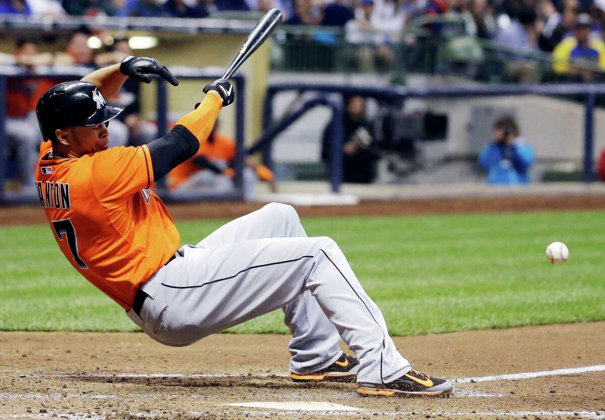 In this photo taken on Thursday, Sept. 11, 2014, Miami Marlins' Giancarlo Stanton falls back after he was hit by a pitch by Mike Fiers during the fifth inning of a baseball game against the Milwaukee Brewers in Milwaukee. Stanton sustained multiple facial fractures, dental damage and cuts that needed stitches after being hit in the face. (AP Photo/Morry Gash)