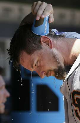 San Francisco Giants starting pitcher Mike Leake pours water over his head to cool off in the dugout during the third inning of a baseball game against the Texas Rangers in Arlington, Texas, Sunday, Aug. 2, 2015. (AP Photo/LM Otero)