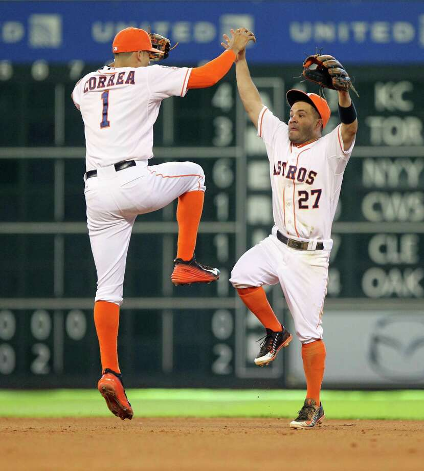 Shortstop Carlos Correa (left) and second baseman Jose Altuve celebrate the Astros' victory over the Diamondbacks on Sunday. C4 Photo: Gary Coronado /Houston Chronicle / © 2015 Houston Chronicle