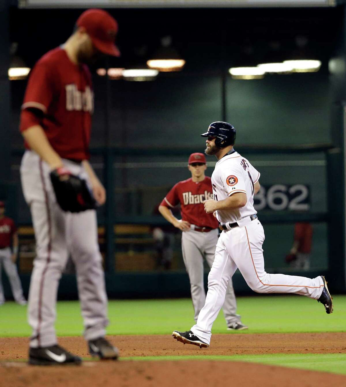 Houston Astros' Evan Gattis, right, runs the bases after hitting a home run off Arizona Diamondbacks starting pitcher Robbie Ray, left, during the fifth inning of a baseball game Sunday, Aug. 2, 2015, in Houston. (AP Photo/David J. Phillip)