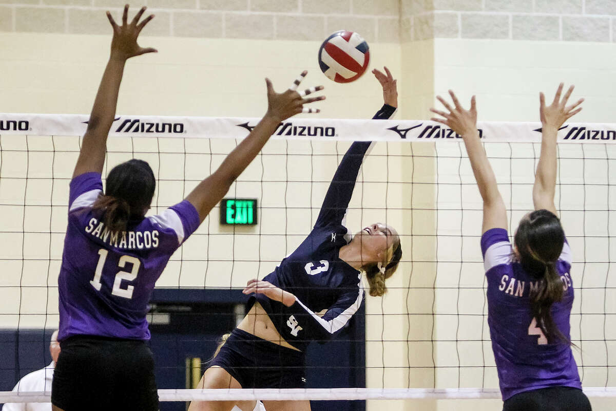 Smithson Valley's Maja Kaiser (center) puts a shot between San Marcos' Broittany Lampkin (left) and Natalie Rios during their district opener at Smithson Valley on Friday, Sept. 27, 2013. Smithson Valley won the match in three straight sets.