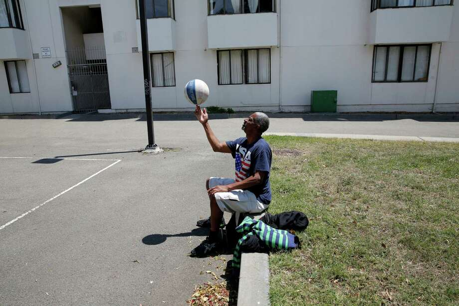 Earlie Jones spins a basketball while watching his sons play at the Buchanan Street Mall. Neighbors are looking for ways to spiff up the public space. Photo: Connor Radnovich / Connor Radnovich / The Chronicle / ONLINE_YES