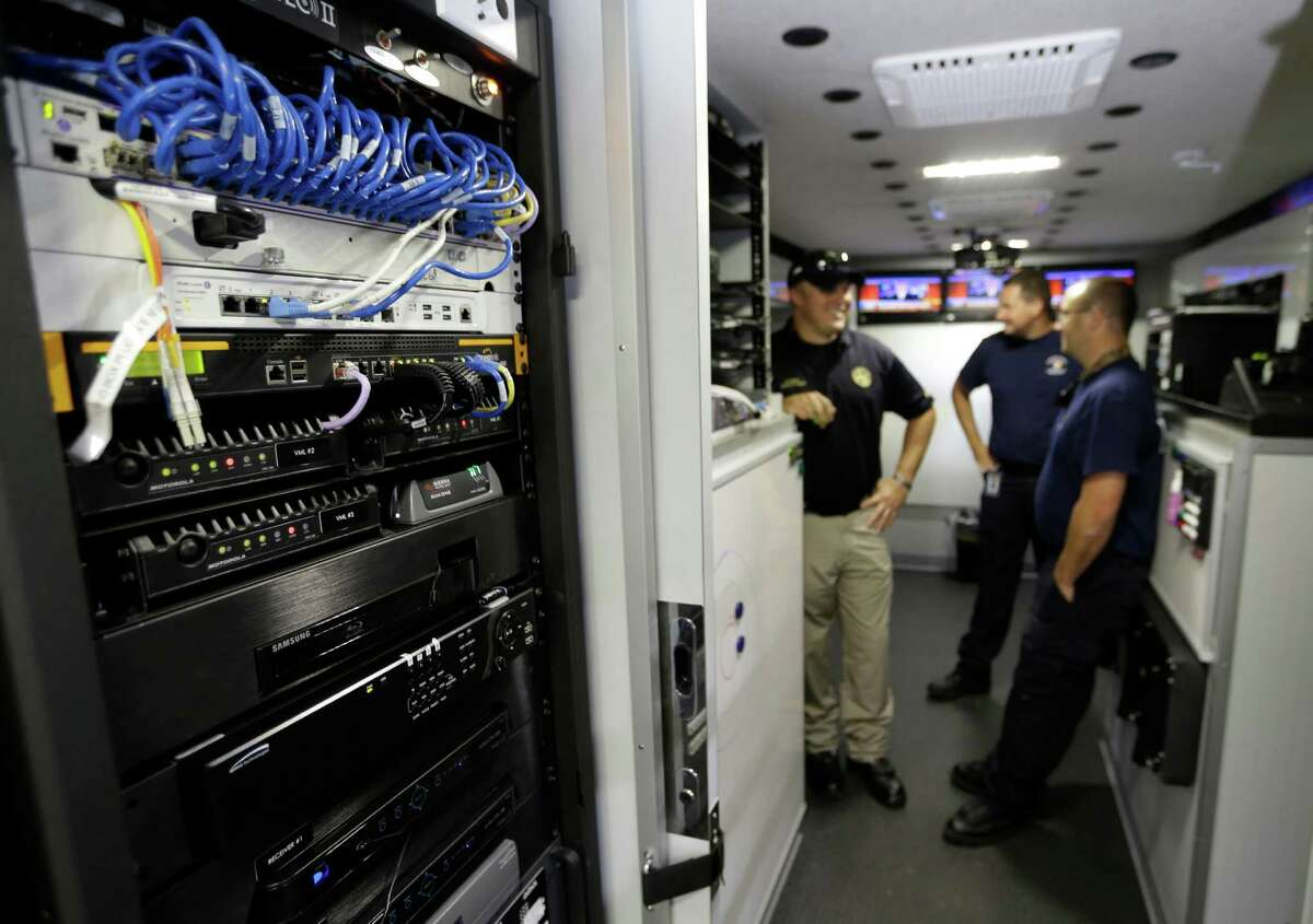 A Hazmat truck's server rack is shown on left as deputy chief Rodney Reed, and Hazmat techs Travis Franzoy and Nathan Mathew, right, all with the Harris County Fire Marshal's Office, talk inside the truck Friday, July 31, 2015, in Humble.