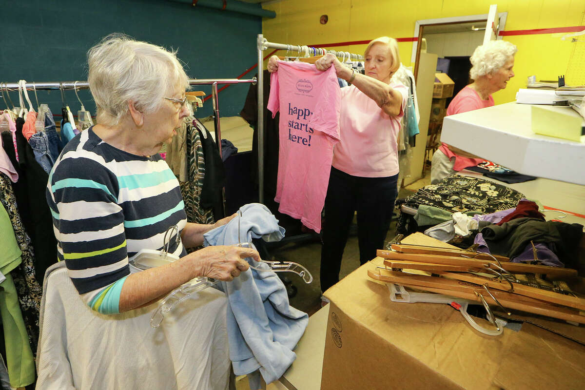 Peg Courtney (from left), Irene Lamprecht and Catherine Hohmann sort donated clothing at the Roy Maas Youth Alternatives Thrift Shop on Monday, July 27, 2015.