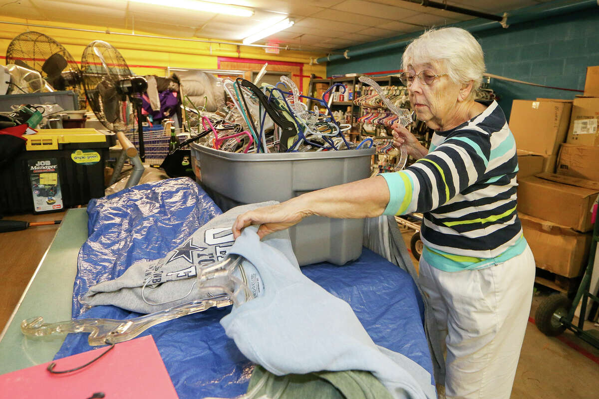 Peg Courtney puts donated clothing on hangars at the Roy Maas Youth Alternatives Thrift Shop on Monday, July 27, 2015.