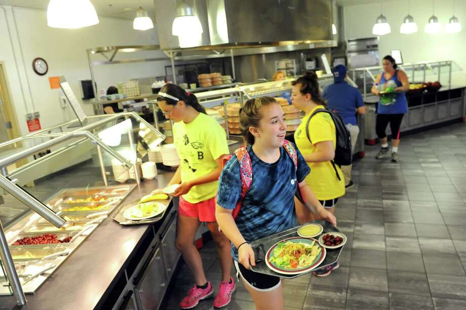 Madeline Gillespie, 14, of Mechanicsburg, Penn., center, picks up her lunch during the Wellspring New York camp on Wednesday, July 15, 2015, at Union College in Schenectady, N.Y. (Cindy Schultz / Times Union) Photo: Cindy Schultz / 00032633A