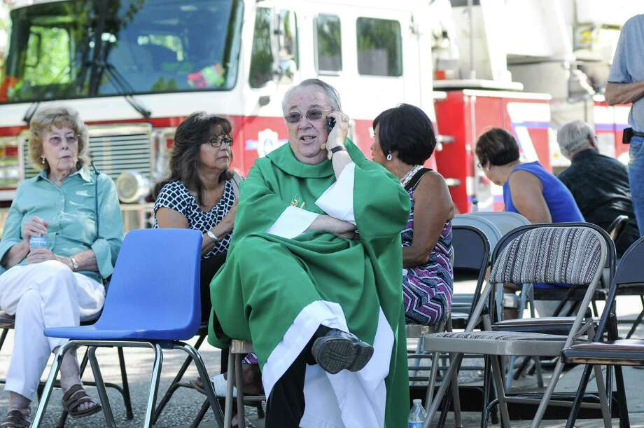 While waiting in a staging area in Las Cruces, N.M., Father John Anderson of Holy Cross Roman Catholic Church tries to reach another local church to warn people to be vigilant. Photo: Robin Zielinski /Las Cruces Sun-News / The Las Cruces Sun-News