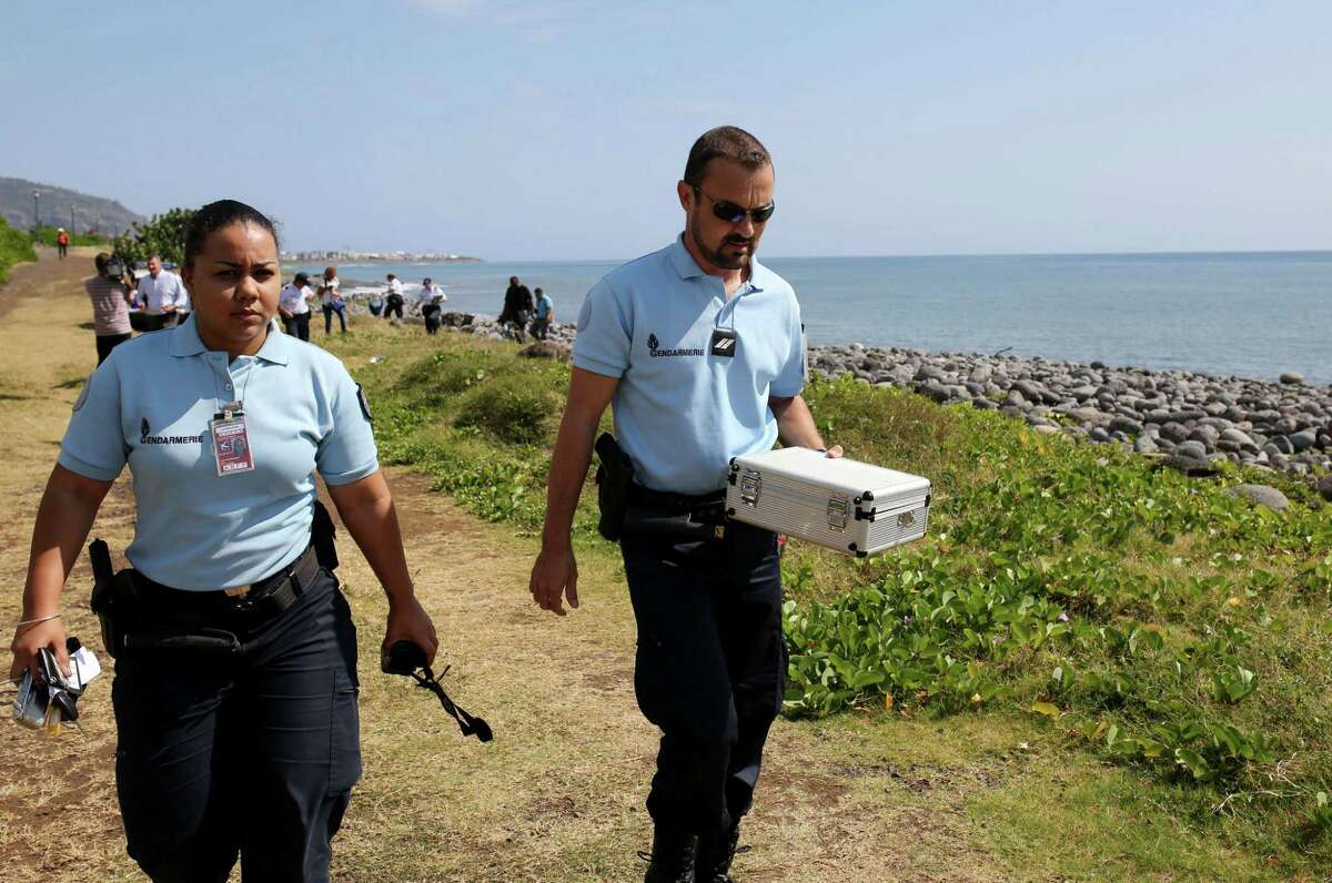 A police officer carries a container holding metallic debris found Sunday on the island of Reunion. The Malaysian director general of civil aviation later said the item was not part of a plane.