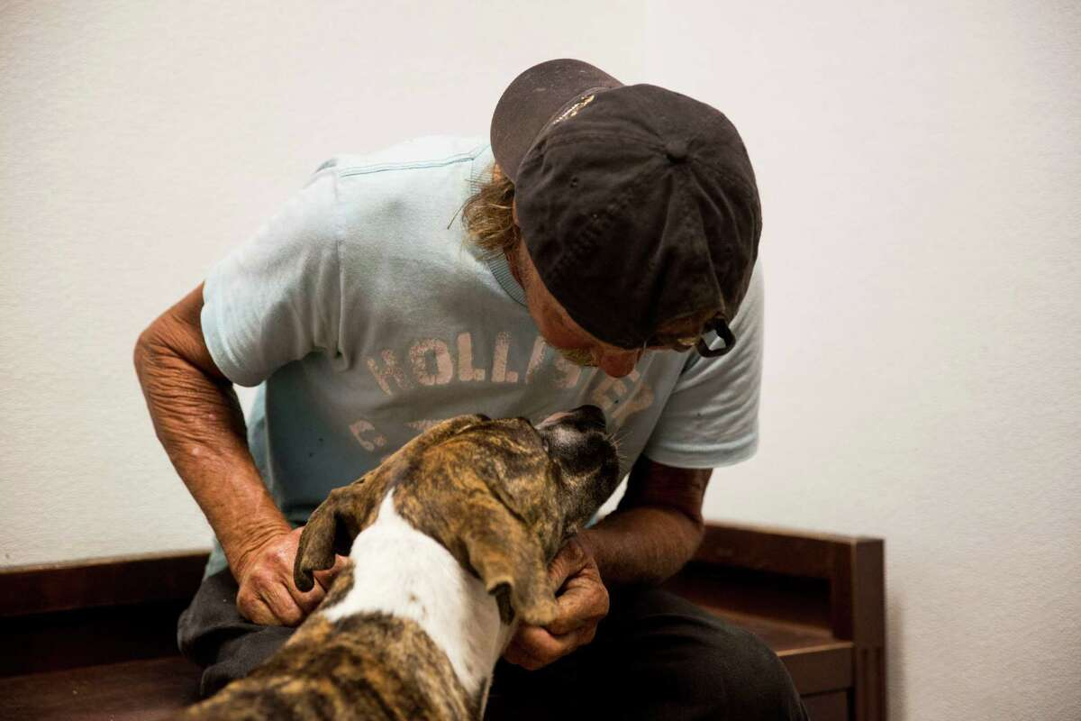 """Matthew """"Jake"""" Smith, 54, reunites with his dog Lady at the Callaghan Road Animal Hospital in San Antonio, Texas on Thursday, July 23, 2015. """"She is everything I've got,"""" Smith said."""