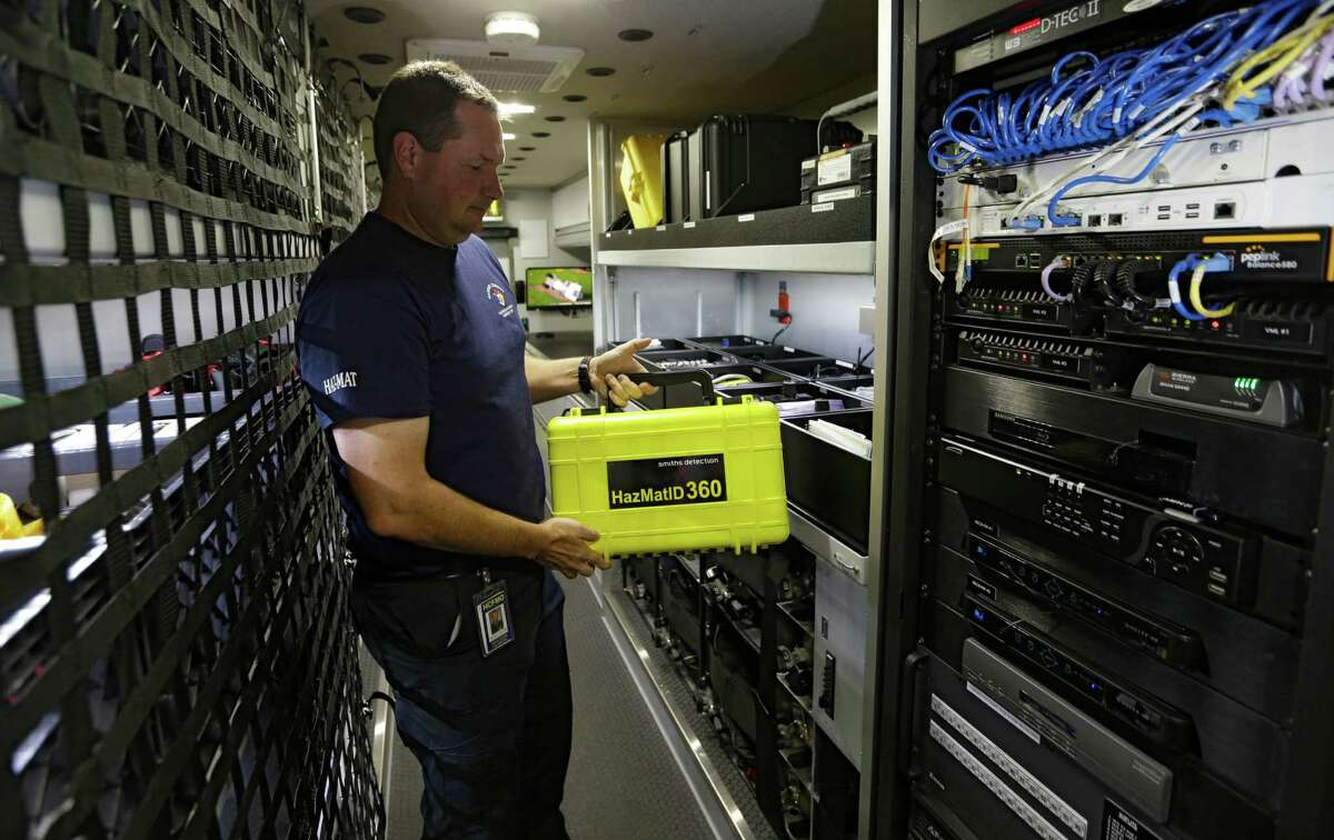 Hazmat tech Travis Franzoy, with the Harris County Fire Marshal's Office, shows some of the equipment on a Hazmat truck, which officials envision can be improved with a public safety data network.