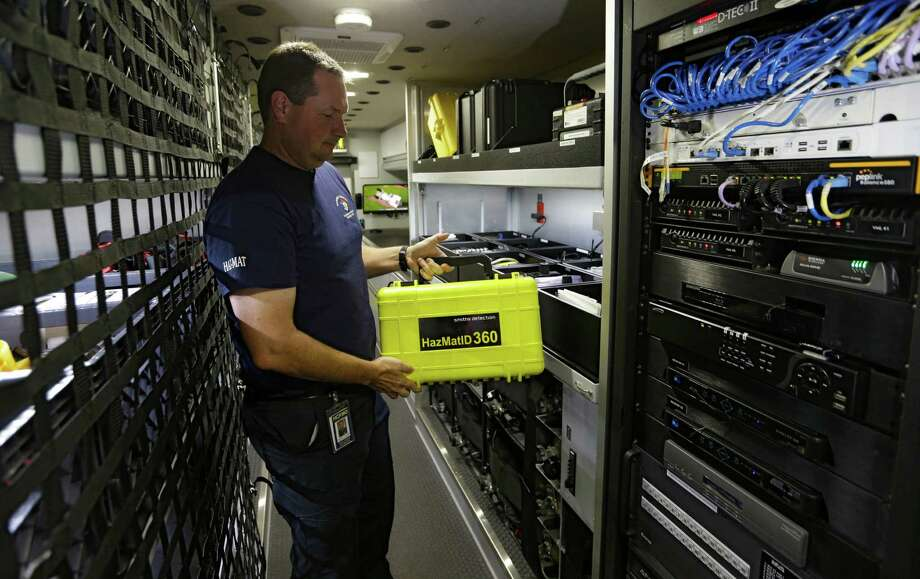 Hazmat tech Travis Franzoy, with the Harris County Fire Marshal's Office, shows some of the equipment on a Hazmat truck, which officials envision can be improved with a public safety data network. Photo: Melissa Phillip, Staff / © 2015 Houston Chronicle