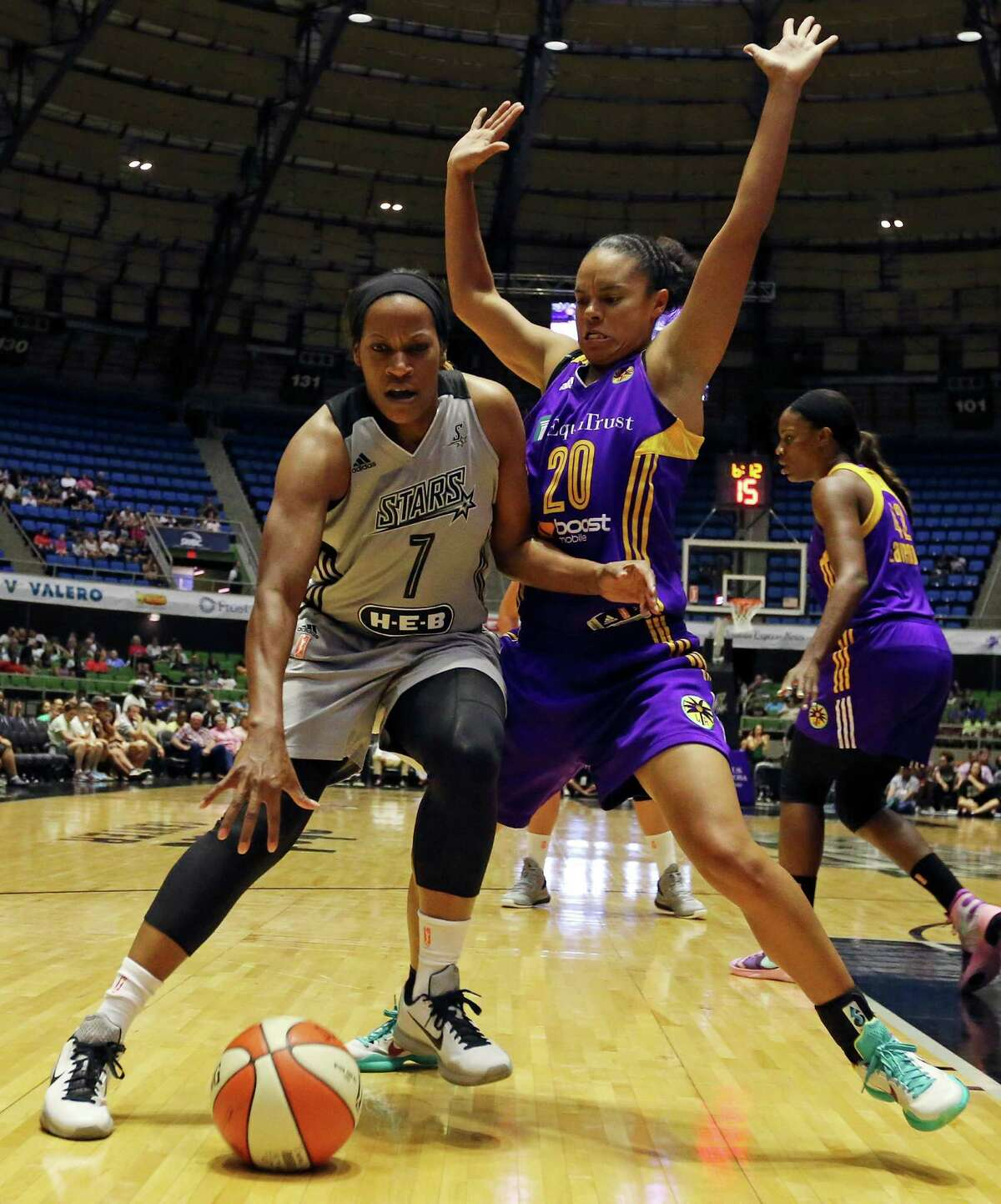 San Antonio Stars' Jia Perkins looks for room around Los Angeles Sparks' Kristi Toliver during first half action Sunday Aug. 2, 2015 at the Freeman Coliseum.