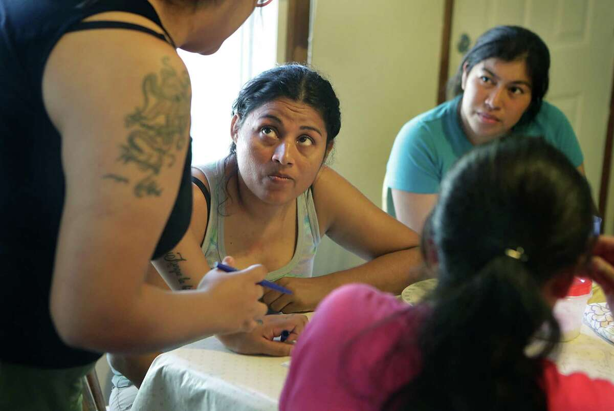Luz Varela, left, a volunteer at a San Antonio shelter, talks to women recently released from South Texas detention centers about their upcoming trips to join family members in the United States.