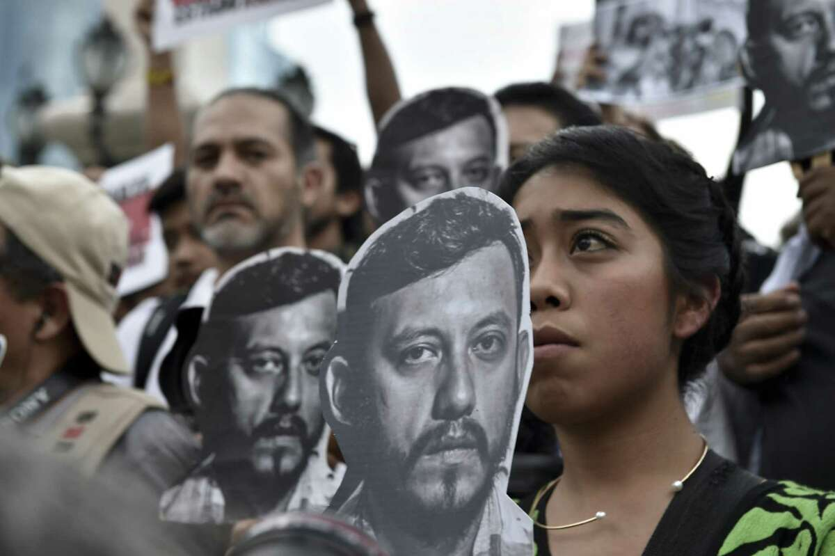 Mexican photojournalists hold pictures of their slain colleague Ruben Espinoza during a demonstration at the Angel of Independence Square in Mexico City.