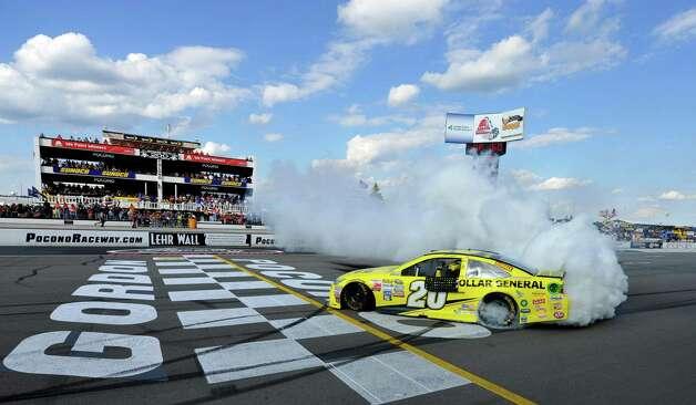 Matt Kenseth smokes his tires after winning the NASCAR Pocono 400 auto race, Sunday, Aug. 2, 2015, in Long Pond, Pa. (AP Photo/Derik Hamilton) ORG XMIT: PAMS109 Photo: Derik Hamilton / FR170553 AP