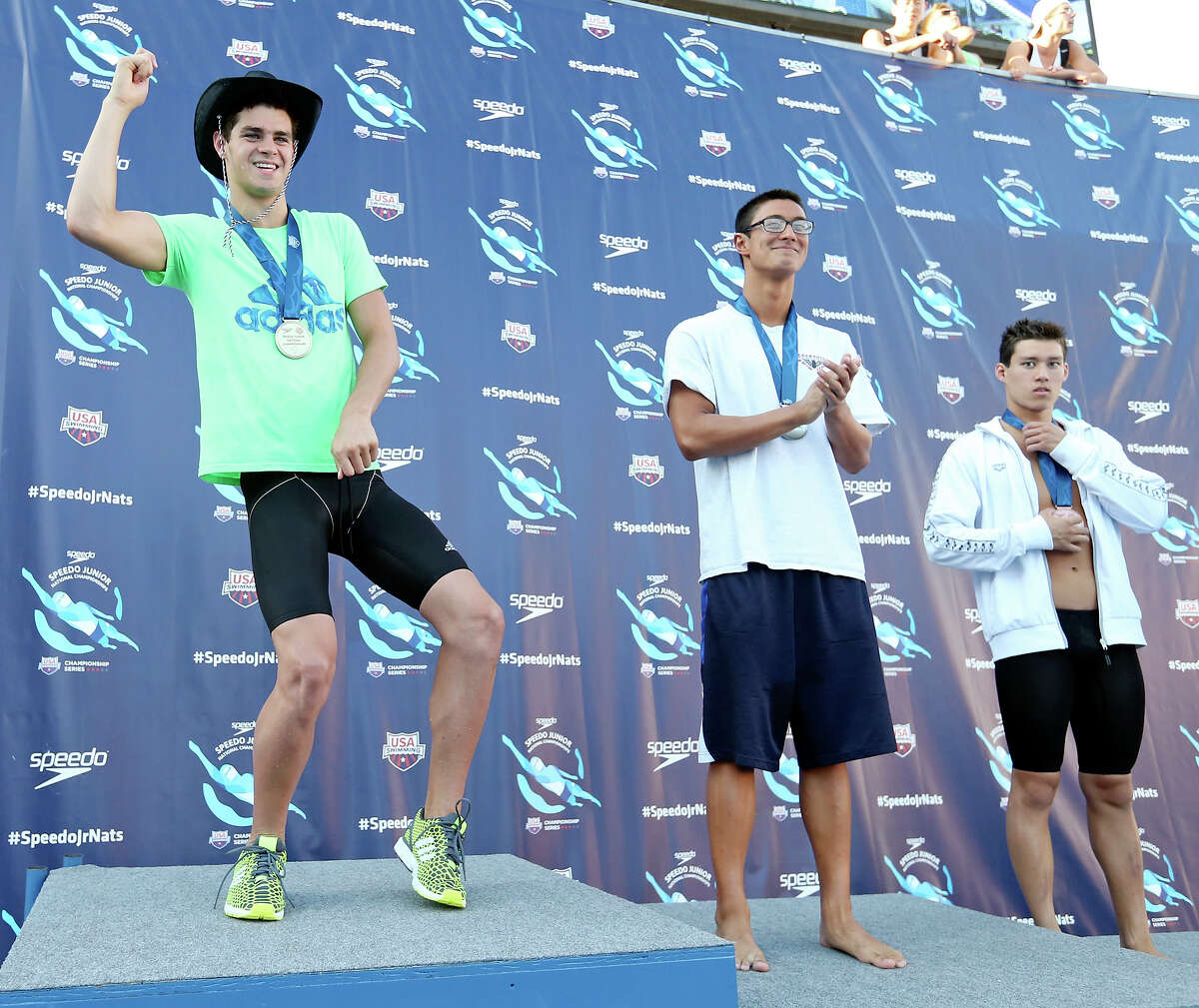 Michael Andrew (from left) jokes on the medal stand with Maxime Rooney and Michael Thomas after Andrew won the 100-meter fly and a cowboy hat at the Speedo Junior Nationals on Saturday at Northside Swim Center.