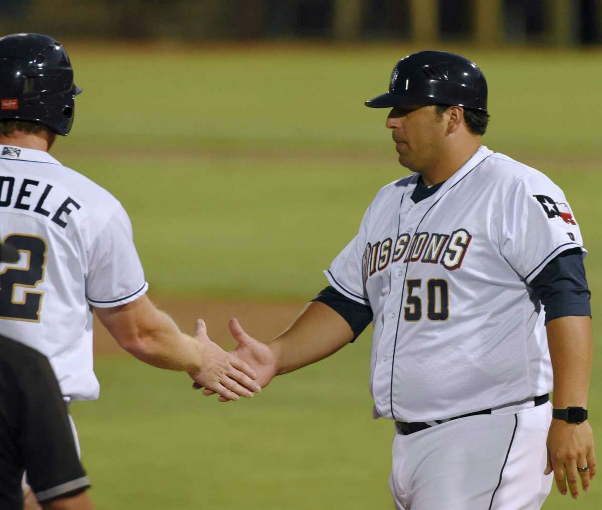 San Antonio Missions manager and third base coach Rod Barajas shakes hands with designated hitter Kyle Gaedele after Gaedele reached third base during Texas League action against Frisco at Wolff Stadium on Saturday, Aug. 1, 2015.