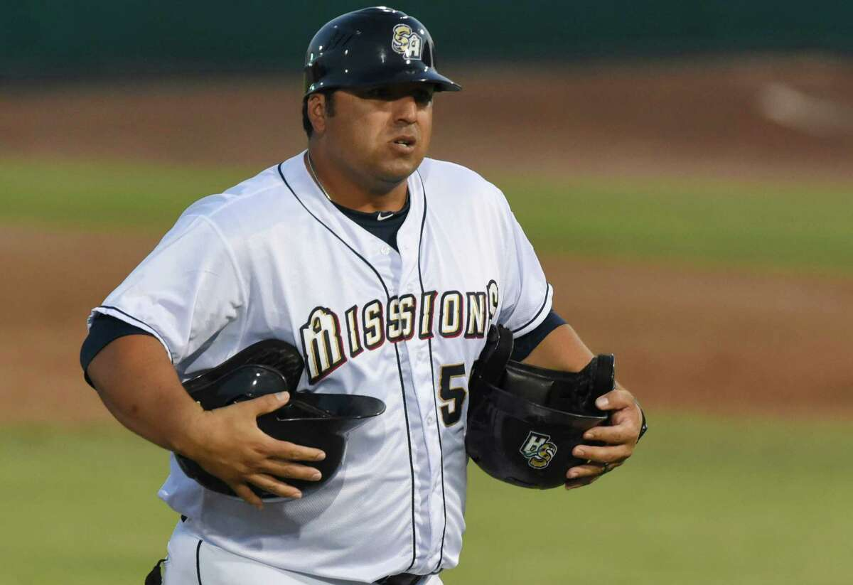 San Antonio Missions manager Rod Barajas carries helmets from the field after the end of an inning during Texas League action against Frisco at Wolff Stadium on Aug. 1, 2015.