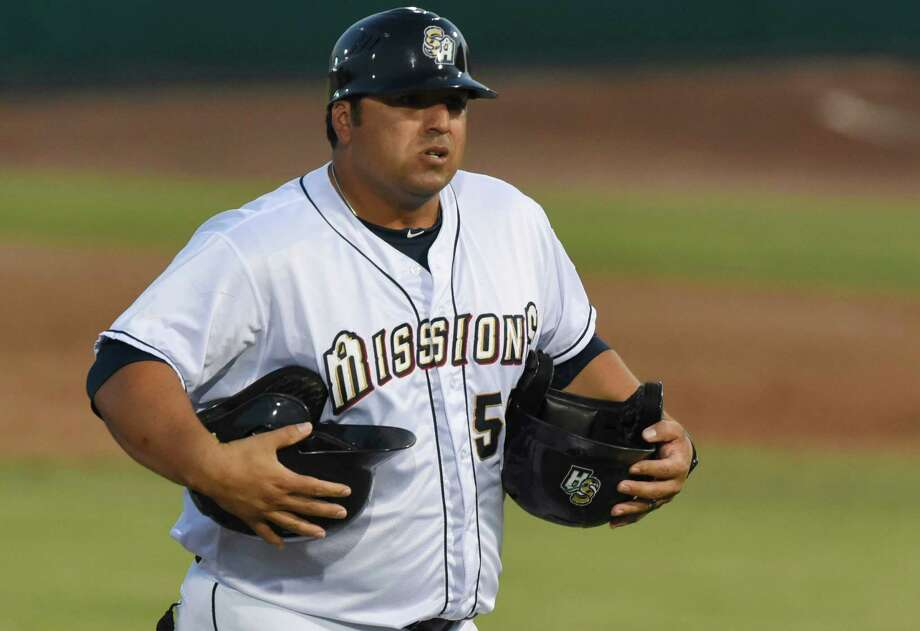 San Antonio Missions manager Rod Barajas carries helmets from the field after the end of an inning during Texas League action against Frisco at Wolff Stadium on Aug. 1, 2015. Photo: Billy Calzada /San Antonio Express-News / San Antonio Express-News