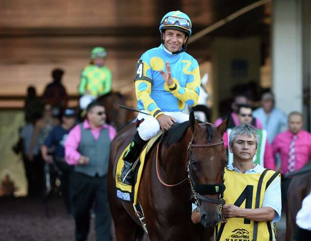 Triple Crown winner American Pharoah with jockey Victor Espinoza heads to the track Sunday Aug. 2, 2015 at Monmouth Park in Oceanport, N.J. for his participation in the 48th running of The Haskel Invitational.    (Skip Dickstein/Times Union) Photo: SKIP DICKSTEIN