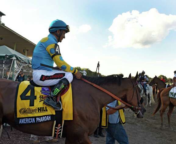 Triple Crown winner American Pharoah with jockey Victor Espinoza heads to the track  Sunday Aug. 2, 2015 at Monmouth Park in Oceanport, N.J. on his way to an easy win in the 48th running of The Haskel Invitational.    (Skip Dickstein/Times Union) Photo: SKIP DICKSTEIN