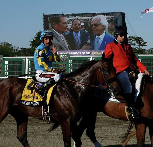 Jockey Victor Espinoza waves to the track as his trainer Bob Baffert is interview in the background Sunday Aug. 2, 2015 at Monmouth Park in Oceanport, N.J. after his an easy win in the 48th running of The Haskel Invitational.    (Skip Dickstein/Times Union) Photo: SKIP DICKSTEIN