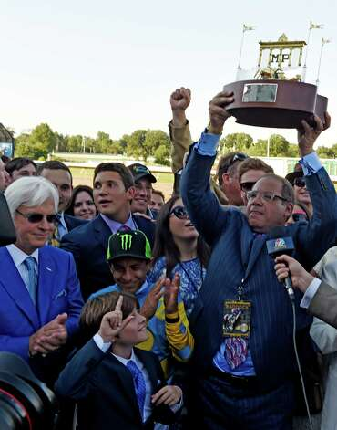 American Pharoah's owner Ahmet Zayat holds the winner's trophy aloft   Sunday Aug. 2, 2015 at Monmouth Park in Oceanport, N.J.after AP's  easy win in the 48th running of The Haskel Invitational.  With Zayat is Trainer Bob Baffert, left and jockey Victor Espinoza, center and Baffert's son Bode, center foreground.    (Skip Dickstein/Times Union) Photo: SKIP DICKSTEIN