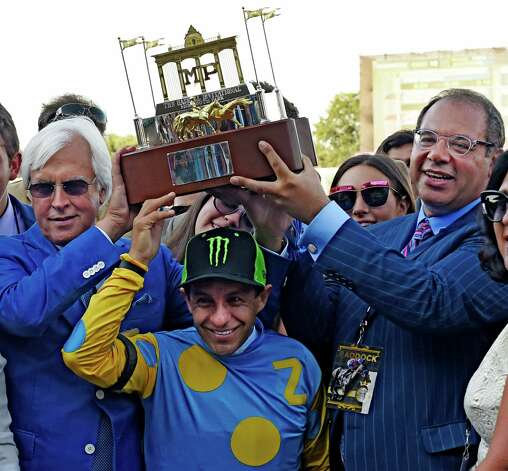 American Pharoah's owner Ahmet Zayat holds the winner's trophy with the help of trainer Bob Baffert, left and jockey Victor Espinpza  Sunday Aug. 2, 2015 at Monmouth Park in Oceanport, N.J. after AP's  easy win in the 48th running of The Haskel Invitational.   (Skip Dickstein/Times Union) Photo: SKIP DICKSTEIN