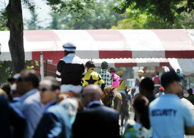 Jockeys and horses head out onto the track for the second race at the Saratoga Race Course on Sunday, August 2, 2015, in Saratoga Springs, N.Y.     (Paul Buckowski / Times Union) Photo: PAUL BUCKOWSKI / 10032858A