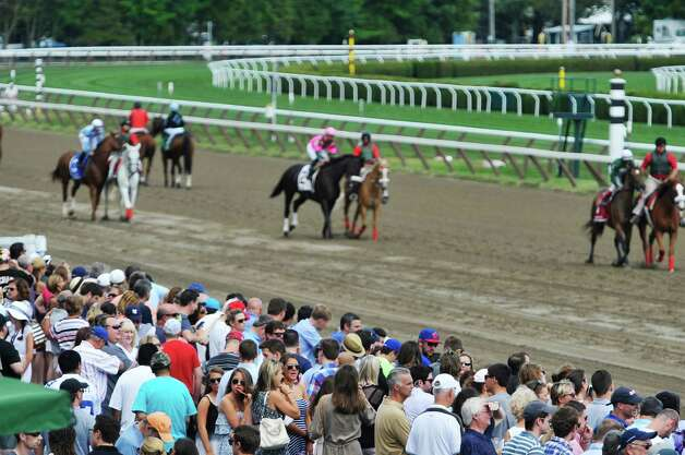 Racing fans watch as the horses and jockeys for the third race parade past them before the start of the race at the Saratoga Race Course on Sunday, August 2, 2015, in Saratoga Springs, N.Y.    (Paul Buckowski / Times Union) Photo: PAUL BUCKOWSKI / 10032858A